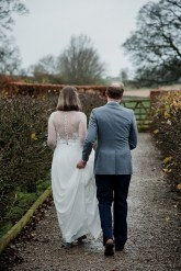 Groom carrying brides dress as they walk along path at Askham Hall