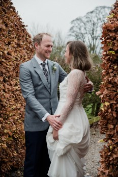 Bride and groom between autumn hedge at Askham Hall