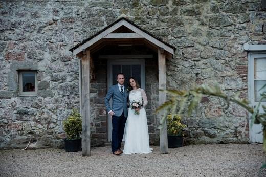Bride and Groom under porch in the gardens of Askham Hall, Cumbria