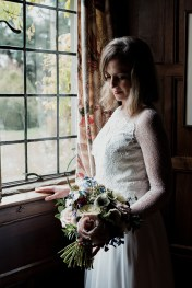 Bride standing in the window of Askham Hall Library