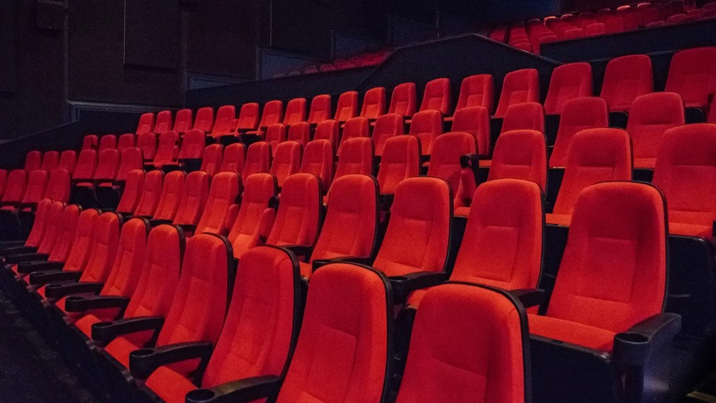 This is a photograph of rows of empty cinema seats inside Genesis Cinema's main auditorium.