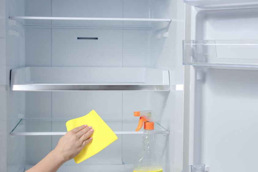Hand cleaning refrigerator. fridge cleaning - spray bottle with detergents for washing the fridge.