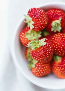 ripe strawberries in white plate on table