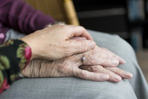 a young person's hand touches the hands of an elder