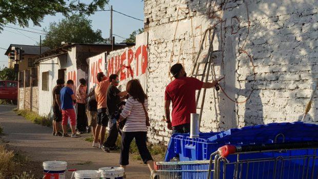 Vecinas y vecinos de la población La Victoria se reunieron este lunes para pintar un mural en recuerdo de Aníbal Villarroel (26), quien murió asesinado en el lugar. Foto: Víctor Pino.