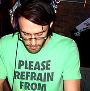 Will Saul with headphones on his head mixing music in a club.