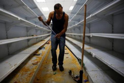 Un trabajador limpia los estantes en un supermercado que fue saqueado en Caracas, Venezuela. 21 de abril 2017.Nueve personas murieron la madrugada del viernes en zonas populares de Caracas, ocho de ellas electrocutadas, durante una nueva jornada de protestas antigubernamentales que derivó en saqueos, dijeron políticos de oposición y un bombero. REUTERS/Carlos Garcia Rawlins