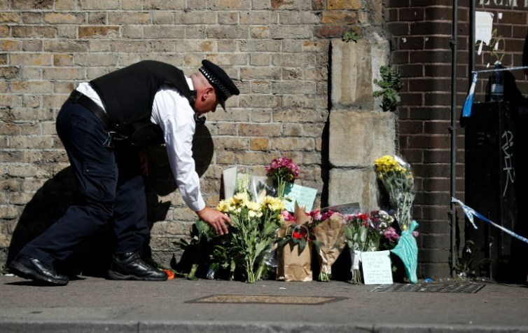 Un policía deja un ramo de flores el 19 de junio de 2017 cerca del lugar en el que un vehículo atropelló a varias personas frente a una mezquita de Finsbury Park, en el norte de Londres  AFP / Tolga Akmen
