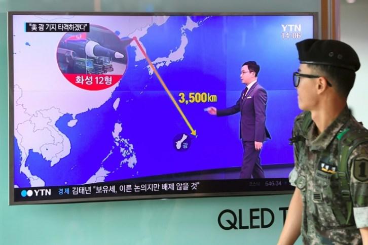 Un soldado pasa junto a una pantalla con un mapa con la distancia entre Corea del Norte y la isla de Guam, el 9 de agosto de 2017 en una estación de trenes de Seúl AFP / Jung Yeon-Je