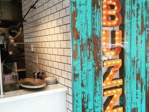 """Le mot """"BUZZ"""" en lumières orange allumées sur un mur en bois vert"""