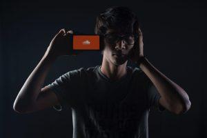 Un homme tient un smartphone avec le logo de SoundCloud à l'écran