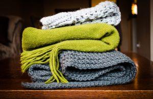 Trois écharpes de gros tissus posées sur une table