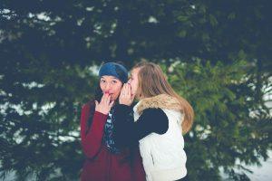 Jeune fille qui chuchote à l'oreille d'une autre
