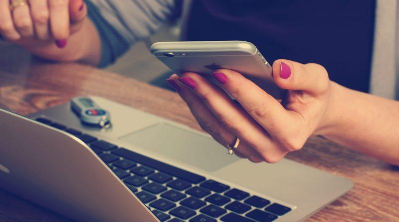 Une femme qui tient un téléphone et navigue sur un ordinateur portable