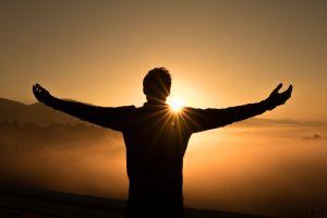 Un homme sur une colline devant un coucher de soleil
