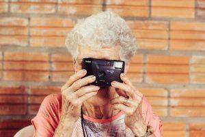 Une aînée tient un appareil photo
