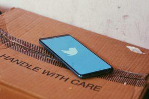 Un téléphone avec le logo Twitter posé sur une boîte