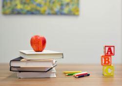 Une pomme posée sur une pile de livres