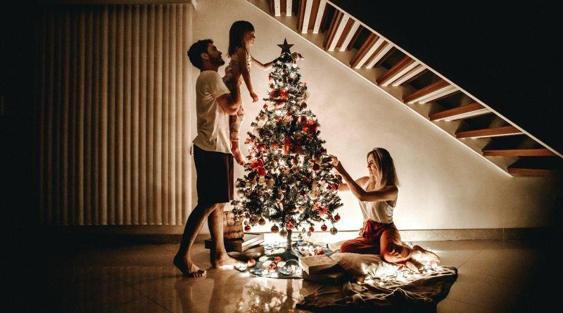 Une famille quiu décore un sapin de Noël