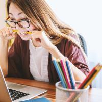 Une femme mord un crayon alors qu'elle est devant l'ordinateur
