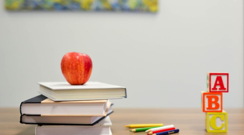 Une pomme et des cubes alphabétiques avec une pile de livres