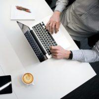 Personne utilisant un ordinateur portable sur une table en bois blanc