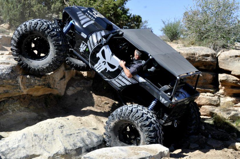 A men driving his black jeep with big tires on rocks