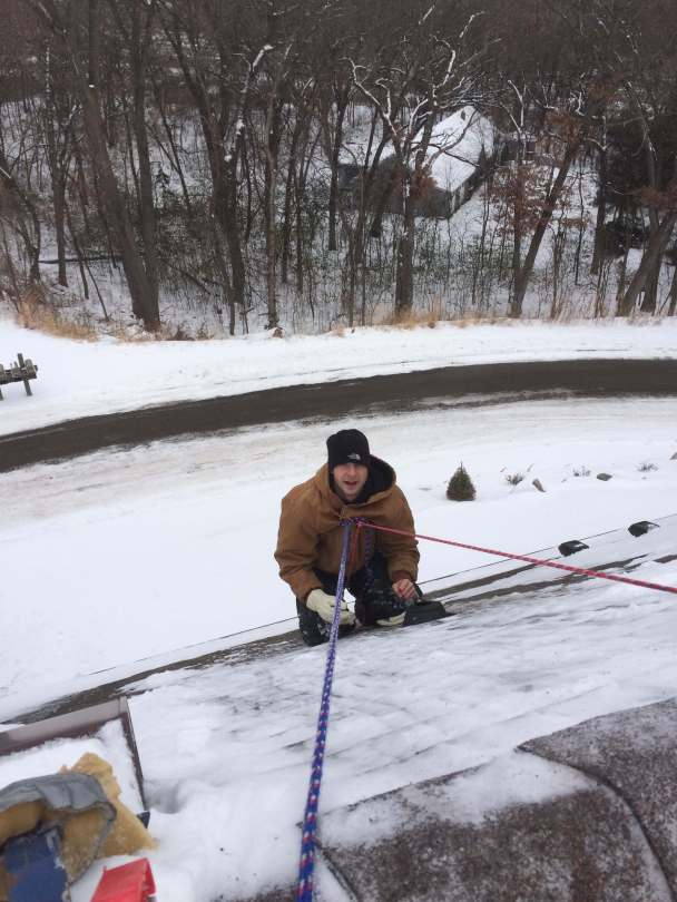 Radon Reduction employee on a snowy roof installing a radon mitigation system vent pipe.
