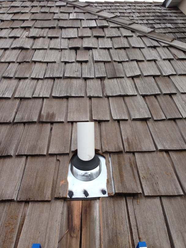 Radon mitigation system vent pipe going through a wood shingle roof.