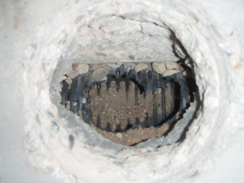 A hole in a concrete floor with a drain tile pipe as part of a radon mitigation system.