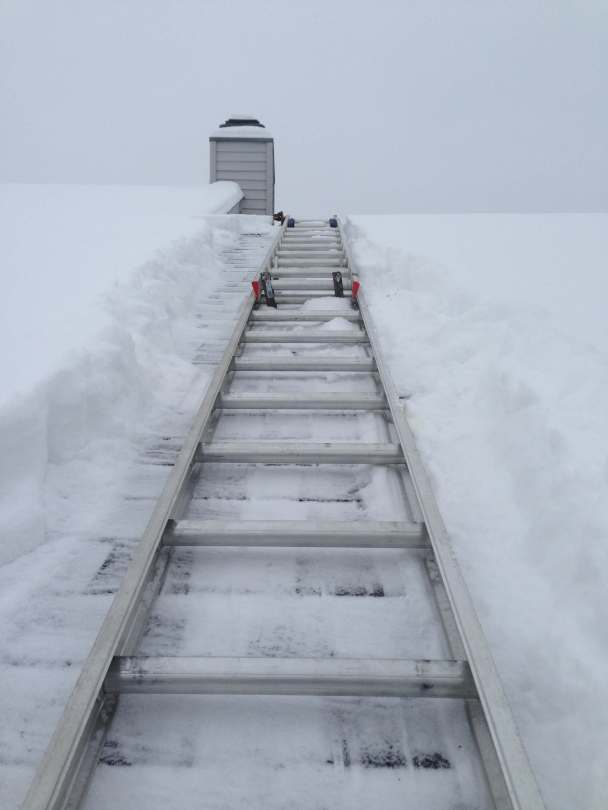 A ladder on a snowy roof to climb to the top.