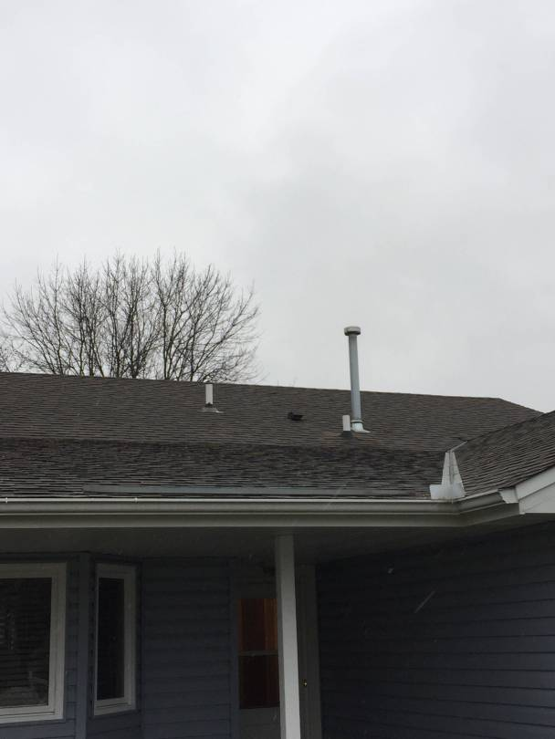 Residential roof with radon mitigation system vent pipe.