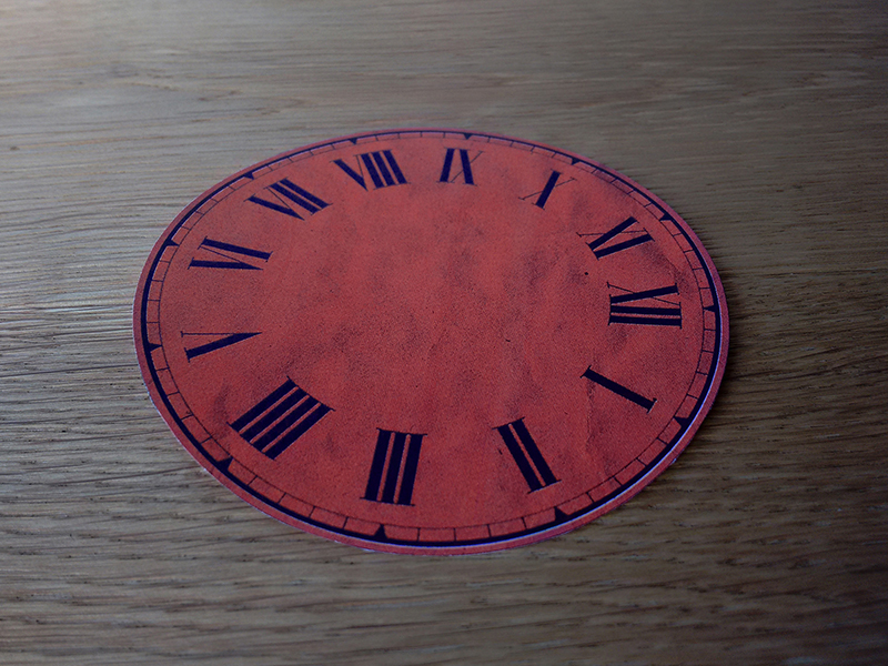 The clock face cutout done with scissors of the bleed line.