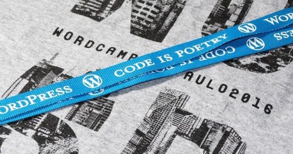 """Camiseta cinza com logo WCSP e cordão azul do WordPress com dizeres """"Code is poetry"""""""