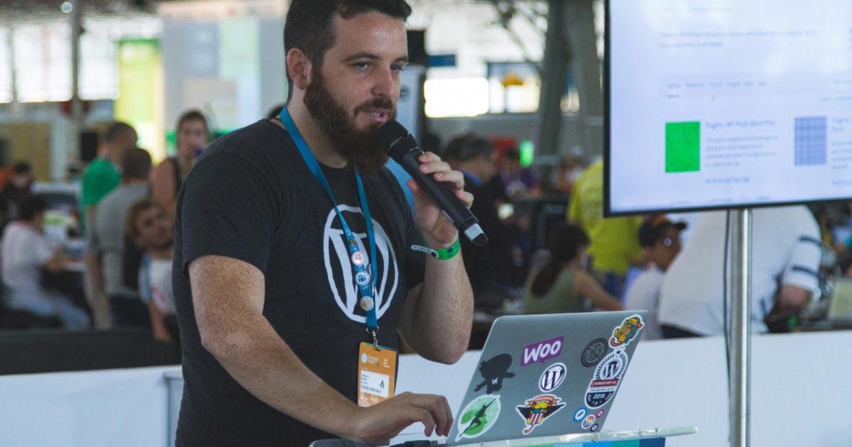 Um barbudo chamado Rafael Funchal vestindo uma camiseta com com um grande W dentro de um círculo (logo do WordPress) segurando um microfone e mexendo em um computador com diversos adesivos do WordPress