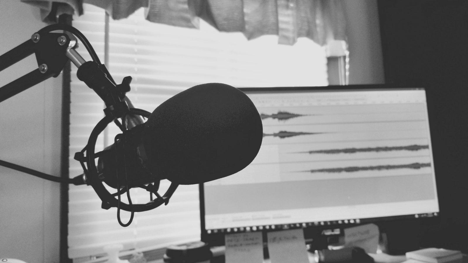 Imagem de um microfone em primeiro plano com um monitor ao fundo com um editor de áudio onde podemos ver duas faixas com ondas sonoras