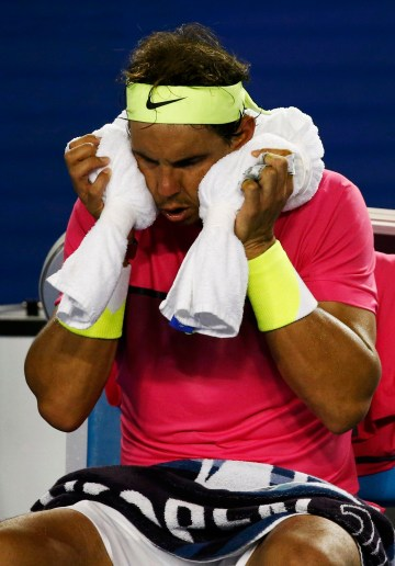 Nadal of Spain wipes his face with an ice pack during his men's singles second round match against Smyczek of the U.S. at the Australian Open 2015 tennis tournament in Melbourne