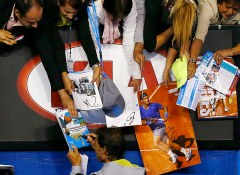 Rafael Nadal of Spain signs autographs after defeating Dudi Sela of Israel in their men's singles third round match at the Australian Open 2015 tennis tournament in Melbourne