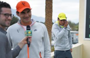 Rafael Nadal speaks on the phone while Roger Federer talks to the media at Indian Wells