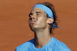 Spain's Rafael Nadal grimaces after missing a shot in the quarterfinal match of the French Open tennis tournament against Serbia's Novak Djokovic at the Roland Garros stadium, in Paris, France, Wednesday, June 3, 2015. (AP Photo/Christophe Ena)