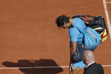 Spain's Rafael Nadal leaves center court while Serbia's Novak Djokovic celebrates winning the quarterfinal match of the French Open tennis tournament in three sets, 7-5, 6-3, 6-1, at the Roland Garros stadium, in Paris, France, Wednesday, June 3, 2015. (AP Photo/Christophe Ena)