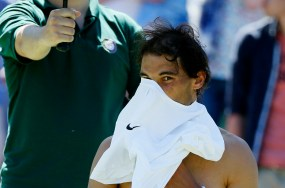 Rafael Nadal of Spain puts a new shirt on during a break between games of his match against Thomaz Bellucci of Brazil at the Wimbledon Tennis Championships in London, June 30, 2015. REUTERS/Stefan Wermuth