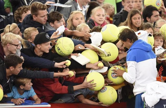 El tenista español Rafael Nadal firma autógrafos tras su victoria ante su compatriota, Fernando Verdasco, durante el partido de primera ronda del torneo de Hamburgo, Alemania, hoy, 28 de julio de 2015. EFE/Daniel Bockwoldt