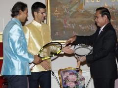 Tennis players Novak Djokovic, center, of Serbia and Rafael Nadal, left, of Spain give rackets to Thai Prime Minister Prayuth Chan-ocha during a meeting at Government House in Bangkok, Thailand Friday, Oct. 2, 2015. Djokovic will face Nadal in the tennis exhibition match in Bangkok to boost confidence in Thailand's safety after a deadly Aug. 17 bombing that left 20 dead in the heart of the capital. (Rungroj Yongrit/Pool Photo via AP)