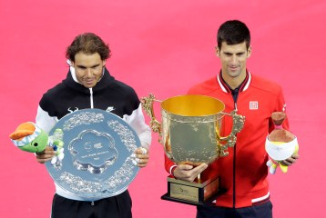 Novak Djokovic of Serbia, right, and Rafael Nadal of Spain hold with their trophies after their men's singles final match in the China Open tennis tournament at the National Tennis Stadium in Beijing, Sunday, Oct. 11, 2015. Djokovic defeated Nadal 6-2, 6-2. (AP Photo/Andy Wong)