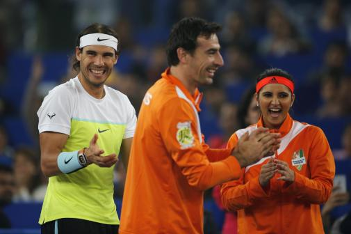 Rafael Nadal, left, Ivan Dodig, centre, and Sania Mirza of the Indian Aces applaud, during International Premier Tennis League in New Delhi, India, Saturday, Dec. 12, 2015. (AP Photo /Tsering Topgyal)