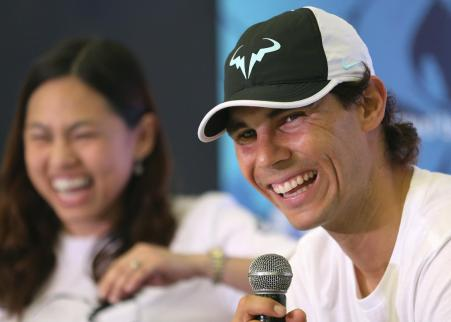 Spain's Rafael Nadal, right, laughs as he answers questions before a tennis clinic in Makati, south of Manila, Philippines Sunday, Dec. 6, 2015. Nadal is in the country to promote his tennis academy and to compete in the International Premier Tennis League (IPTL). (AP Photo/Aaron Favila)