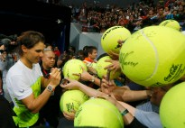 Spain's Rafael Nadal of the Indian Aces autographs large tennis balls for Filipino fans following his win over Canada's Milos Raonic of the Philippine Mavericks in the men's singles match of the 2015 International Premier Tennis League Tuesday, Dec. 8, 2015 at the Mall of Asia Arena at suburban Pasay city south of Manila, Philippines. Nadal won the thrilling shootout 6-5 (7/6). (AP Photo/Bullit Marquez)