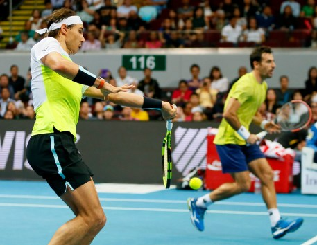 Spain's Rafael Nadal, left, of the Indian Aces hits a forehand as he teams up with Croatia's Ivan Dodig during the men's doubles match against Philippine Mavericks' Richard Gasquet and Edouard Roger-Vasselin of France in the 2015 International Premier Tennis League Tuesday, Dec. 8, 2015 at the Mall of Asia Arena at suburban Pasay city south of Manila, Philippines. The Indian Aces won. (AP Photo/Bullit Marquez)