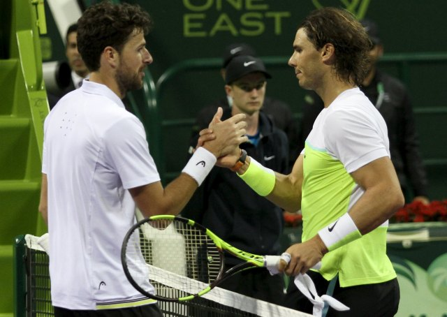 Rafael Nadal of Spain shakes hands with Robin Haase of the Netherlands after their Qatar Open men's singles tennis match in Doha, Qatar January 6, 2016. REUTERS/Naseem Zeitoon